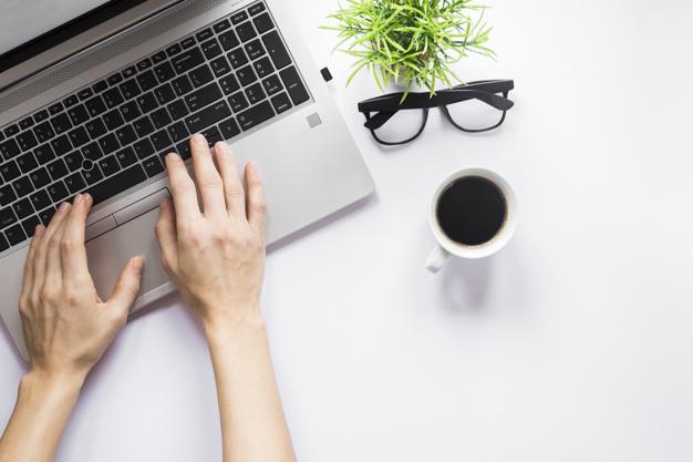 Foto Gratis | Primer plano de la mano de una persona escribiendo en la  computadora portátil con una taza de café; anteojos y planta de maceta en  el escritorio blanco